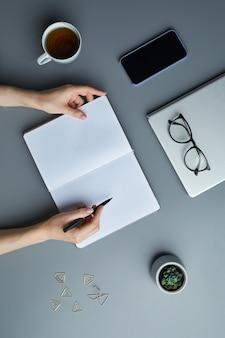 회색 직장에서 작업하는 동안 빈 흰색 플래너에서 작성하거나 스케치하는 여성 손의보기 배경 위,