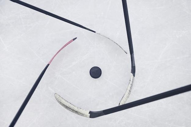 スケートリンクで試合を開始する準備ができてプルを回っているホッケークラブのビューの背景の上