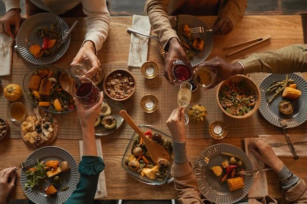 Выше вид на фоне многонациональной группы людей, наслаждающихся застольем во время обеда с друзьями и семьей