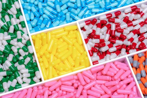 上の図のプラスチックの箱のカプセルの丸薬。マルチカラーカプセルピル。ビタミンとサプリメントの概念。製薬業界。薬局製品。ヘルスケアと医学。医薬品製造。