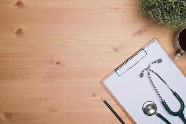 Надпись на доске сзажимом для бумаги, кофейная чашка и стетоскоп на рабочем месте врача.