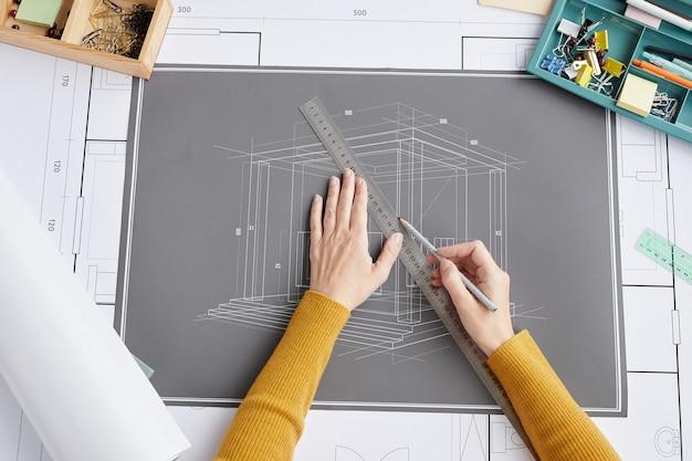 위의보기는 사무실에서 책상에 앉아있는 동안 청사진과 계획을 그리는 여성 건축가의 닫습니다.