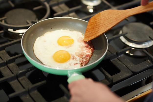 보기 위의 팬, 복사 공간에 계란 튀김에 초점을 맞춘 가정 부엌에서 아침 식사를 요리하는 인식 할 수없는 여자의 닫습니다