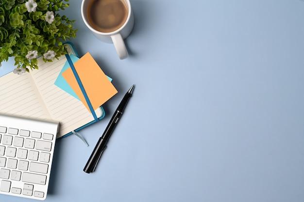 Выше вид удобное рабочее место с чашкой кофе, ноутбуком, заводом и клавиатурой на синем фоне.