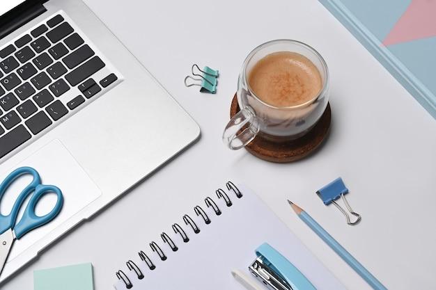 Выше посмотрите чашку кофе, портативный компьютер и блокнот на белом столе.