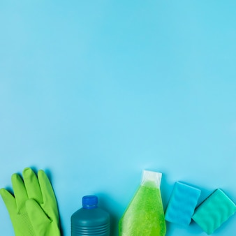 Вид сверху на расположение бутылочек с моющими средствами и перчаток