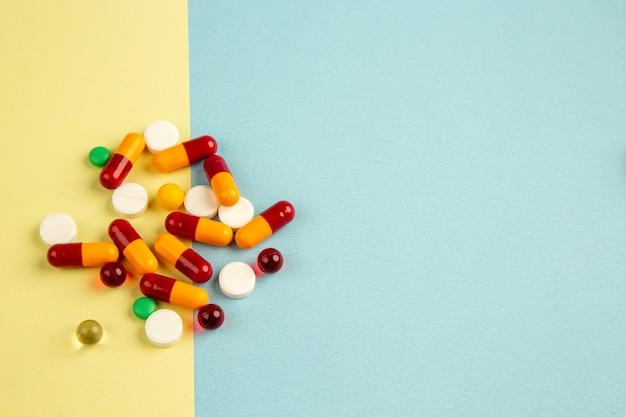 Вид сверху разные таблетки на желто-синей поверхности пандемический цвет больница covid- наука вирус здоровья лаборатория свободное пространство для лекарств