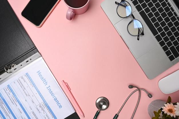 보고서, 청진기, 노트북 및 스마트 폰이 있는 보기 의사 작업 공간 위.