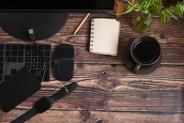 Выше вид пустой блокнот, умные часы и кофейную чашку на деревянном столе.