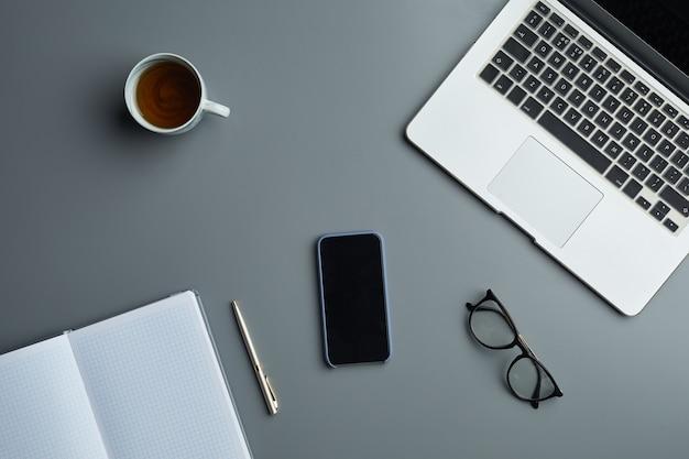 灰色の職場の背景にノートパソコンとビジネスアクセサリーの平面図の上