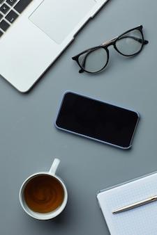 上図コーヒーカップと灰色の職場の背景にラップトップとスマートフォンのフラットレイ、