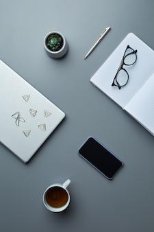 上図コーヒーカップとスマートフォンと灰色の職場の背景にスマートフォンと空白のプランナーのフラットレイ、
