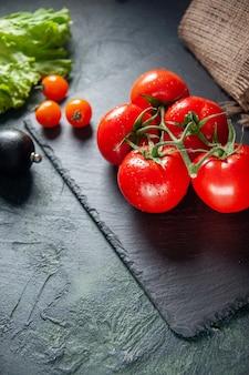 上は暗い背景に新鮮な赤いトマトを表示します