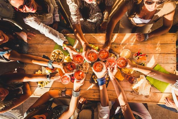 上のビューの友人のグループは、人々が一緒に持っている赤ワイングラスで乾杯し、チャリンという音を立てて食べ物や飲み物を楽しんでいます。楽しい