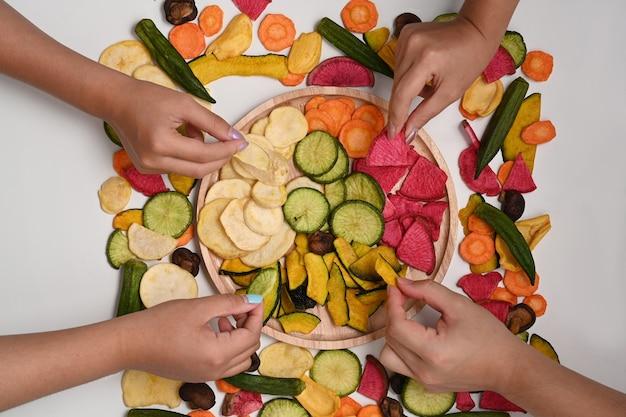 ミックス野菜チップスを食べている若者の上のビューグループ。