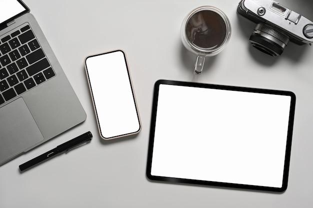 Выше вид портативный компьютер, цифровой планшет, смартфон и камера на белом столе.