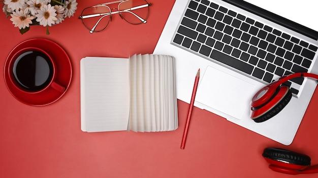 上図のラップトップコンピューター、ノートブック、赤い背景のコーヒーカップ。