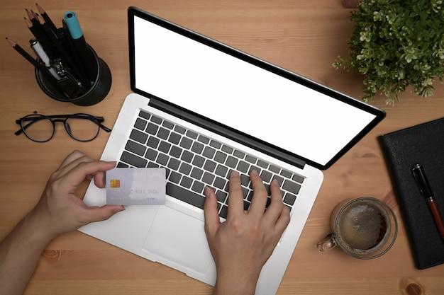 上の図は、ラップトップコンピューターを使用して、オンラインで買い物や銀行取引をするために携帯電話を持っている男性です。