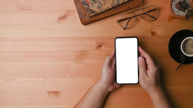 上図木製の机の上の空の画面でモックアップスマートフォンを保持している男の手。
