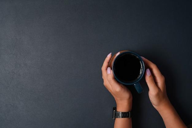 Выше вид мужчина держит чашку горячего напитка на черной коже.