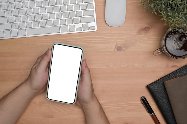 Выше вид человек, держащий смартфон с белым экраном.