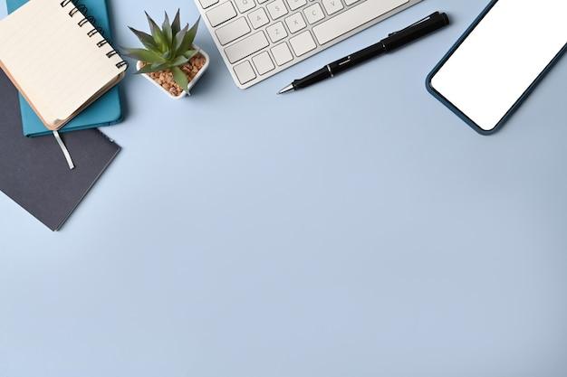 Выше вид мобильного телефона, клавиатуры и ноутбука на синем фоне.