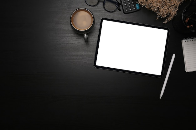 위의 보기는 디지털 태블릿, 스타일러스 펜 및 커피 컵을 검은색 테이블에 조롱합니다.