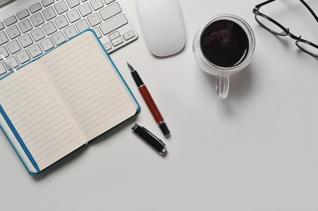 Выше вид ноутбук, чашка кофе и очки и клавиатура на белом офисном столе.