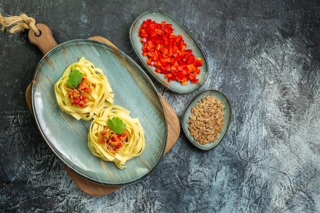 어두운 탁자에 있는 재료 옆에 있는 도마 위에 토마토와 고기가 곁들여진 맛있는 파스타 식사가 있는 파란색 접시의 전망