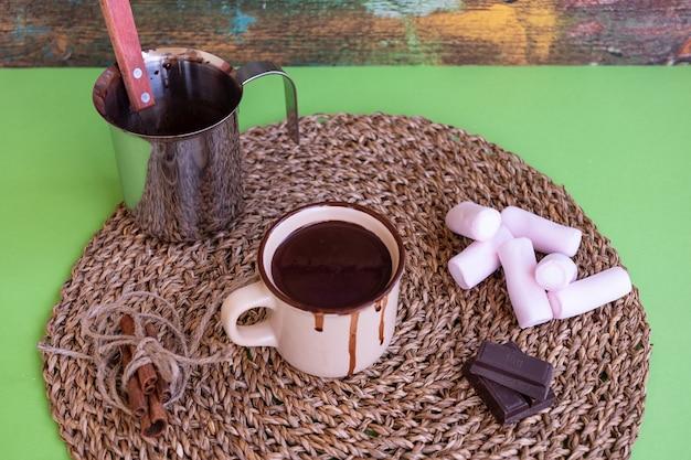 ホットで濃厚でクリーミーなダークチョコレートが入ったセラミックカップの上の図。マシュマロ、シナモン、チョコレートのかけらが入った素朴なランチョンマット