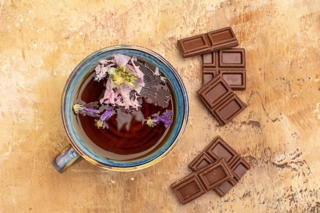 Выше вид на чашку горячего травяного чая и плитки шоколада на столе смешанного цвета