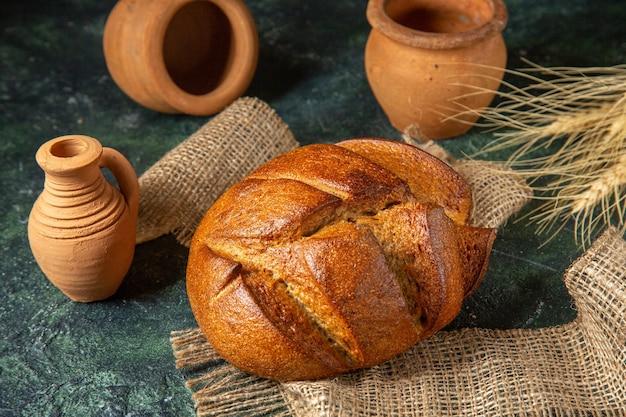Выше вид на буханку диетического черного хлеба на коричневом полотенце и гончарные изделия на поверхности темных цветов