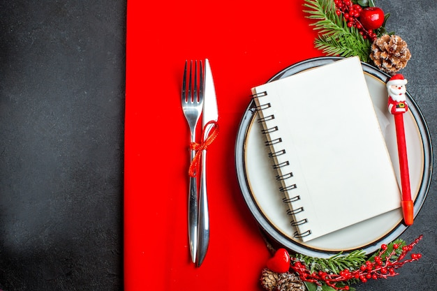 Выше вид спирального блокнота и ручки на обеденной тарелке с декоративными аксессуарами еловыми ветками и набором столовых приборов на красной салфетке