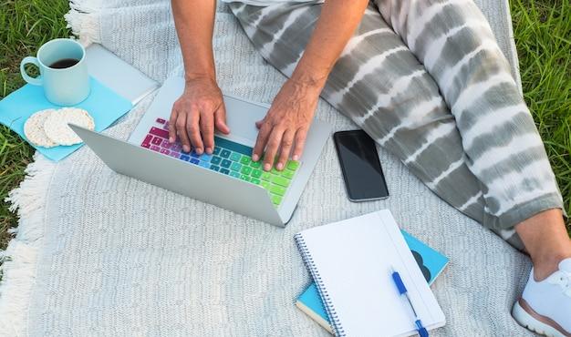 Выше вид повседневной одежды пожилой женщины, сидящей на лугу и работающей с ноутбуком. чашка кофе и диетическое печенье рядом с ней