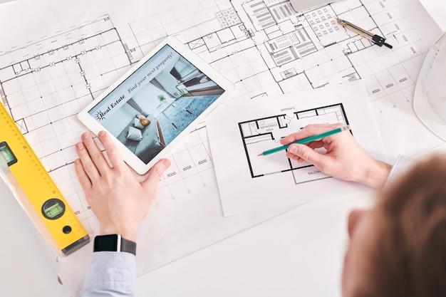 フラットの平面図に取り組んでいる間デジタルタブレットと青写真を使用している建築家のビューの上