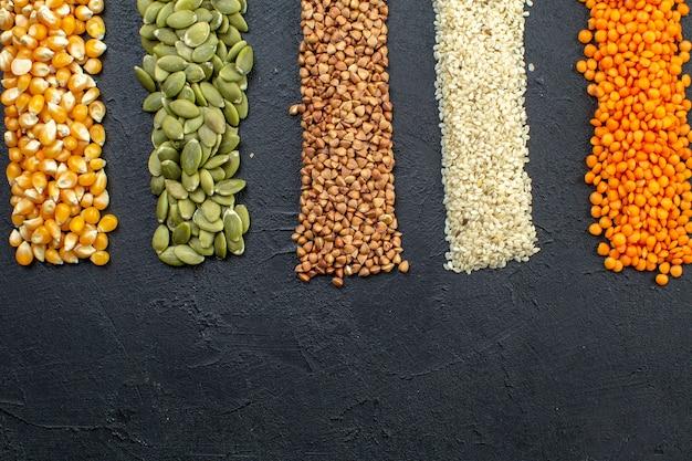검은 배경에 메밀 호박 씨앗 붉은 렌즈콩 쌀 옥수수의 여러 곡물의 보기 위에