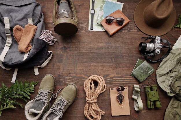 バックパック、ロープ、ブーツ、コンパス、双眼鏡、帽子、ランタン、木製テーブルの地図の上のビュー