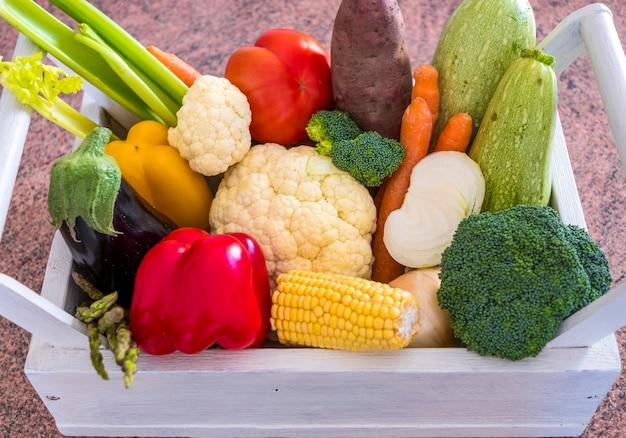 さまざまな種類の新鮮な野菜でいっぱいのバスケットのビューの上に健康的な食事の概念