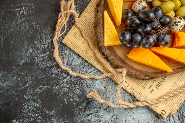오래된 신문에 있는 나무 갈색 쟁반 밧줄에 다양한 과일과 음식을 넣은 최고의 간식