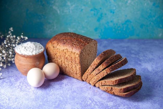 空きスペースのある水色のパターンの背景に黒いパンのスライス小麦粉の卵の上のビュー
