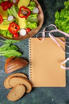 Выше вид на ломтики черного хлеба, свежие нарезанные овощи на тарелке и спиральный блокнот с зеленой связкой на темной поверхности