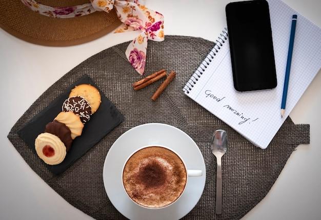 우유 거품과 코코아 가루, 둥근 비스킷이 있는 흰색 탁자 위에 있는 카푸치노 한 잔과 함께 아침 식사 코너의 전망 - 스마트 폰 및 메모장