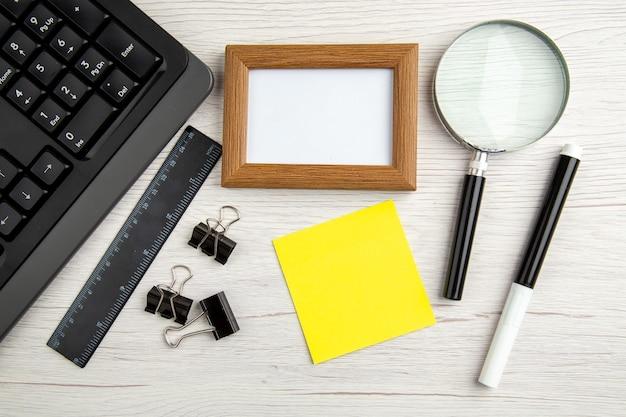 Выше вид коричневой пустой фоторамки и полушапка ноутбука, линейки, маркера, увеличительного стекла, скрепок на белом