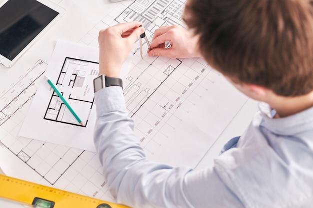 机に座って、フラットの平面図に取り組んでいる間コンパスのペアを使用して建物のエンジニアのビューの上
