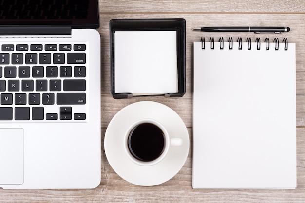 ビジネスマンの職場のビューの上。一杯のコーヒー、ラップトップ、ノートブック、ペン。ビジネス、教育またはブログの概念。