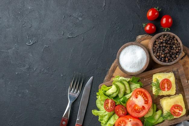 まな板の上に刻んだ新鮮な野菜のチーズと、黒い表面にセットされたスパイス カトラリーのビューの上