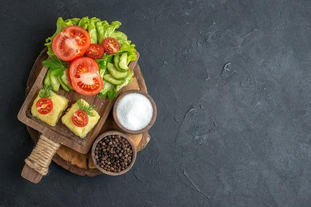 まな板の上に刻んだ丸ごとの新鮮な野菜と黒い表面にスパイスが置かれているビューの上