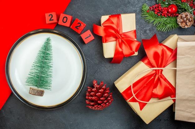 Вид сверху елки на тарелке, хвойные шишки, еловые ветки, цифры, красивые подарки на темном столе