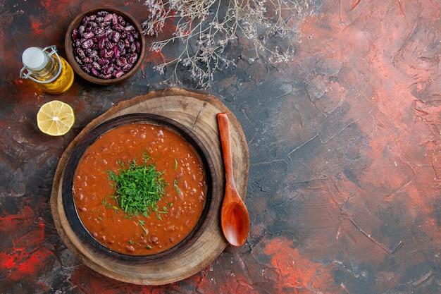 混合色のテーブルの上の茶色のボウルオイルボトル豆とスプーンの古典的なトマトスープのビューの上
