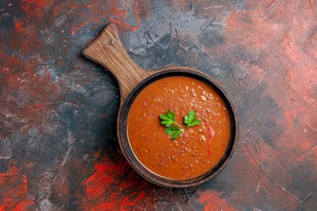 混合色のテーブルの茶色のまな板の上の古典的なトマトスープのビューの上